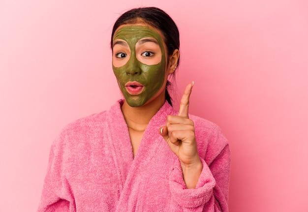 Młoda kobieta wenezuelska ubrana w szlafrok i maskę na twarz na białym tle na różowym tle mająca pomysł, koncepcję inspiracji.