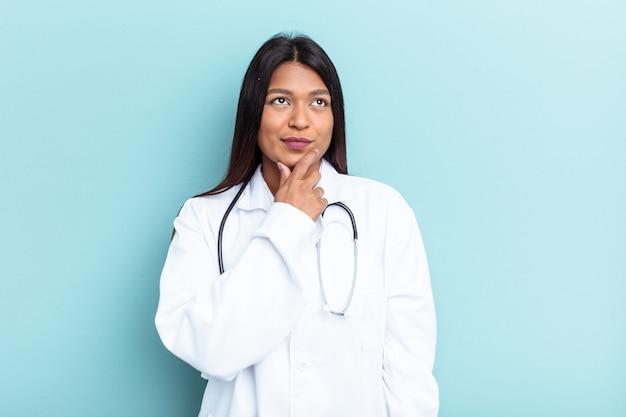 Młoda kobieta wenezuelskiej lekarza na białym tle na niebieskim tle patrząc z boku z wyrazem wątpliwości i sceptyczny.