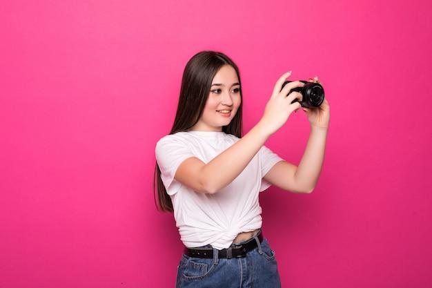 Młoda kobieta wesoła z aparatu fotograficznego na różowej ścianie
