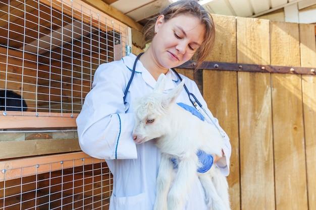 Młoda kobieta weterynarii z stetoskop gospodarstwa i badanie koza dziecko na tle ranczo. młoda koźlątka w rękach weterynarza do sprawdzenia w naturalnej ekologicznej farmie. nowoczesne zwierzęta gospodarskie, rolnictwo ekologiczne.
