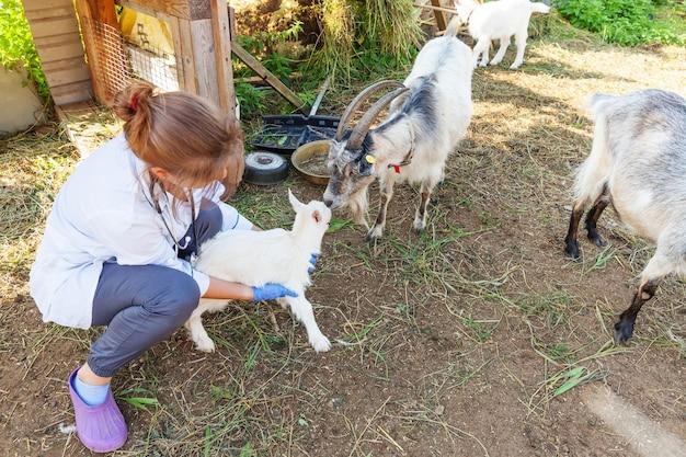 Młoda kobieta weterynarii z stetoskop gospodarstwa i badanie koza dziecko na tle ranczo. młody koźląt w rękach weterynarza do sprawdzenia w naturalnej ekologicznej farmie. nowoczesne zwierzęta gospodarskie, rolnictwo ekologiczne.