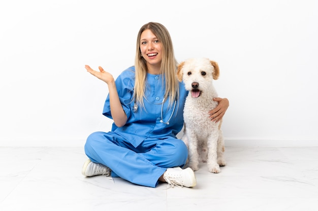 Młoda kobieta weterynarz z psem siedzi na podłodze wyciągając ręce na bok za zaproszenie do przyjścia
