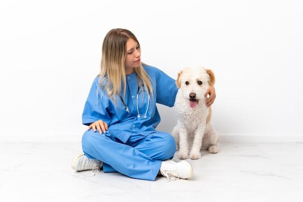 Młoda kobieta weterynarza z psem, siedząc na podłodze