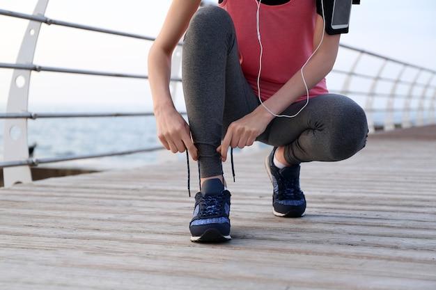 Młoda kobieta wiążąca sznurowadła podczas porannego biegu