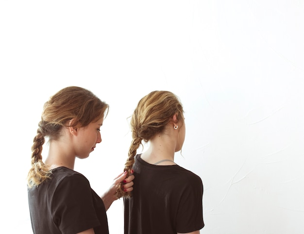 Młoda kobieta wiąże jej siostry włosy odizolowywającego nad białym tłem