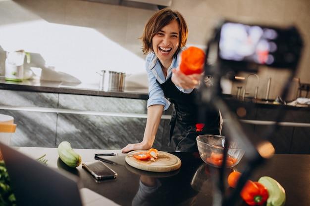 Młoda kobieta wideoblogger gotowania w kuchni i filmowanie