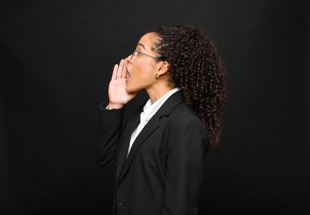 Młoda kobieta widok profilu, patrząc szczęśliwy i podekscytowany, krzycząc i wzywając do kopiowania miejsca na boku na czarnej ścianie