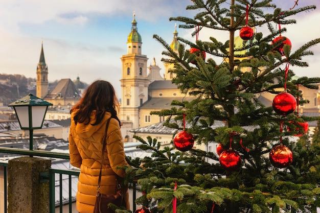 Młoda kobieta widok z tyłu stoi na pogodnym bożenarodzeniowym salzburg, austria. choinki z czerwonymi bombkami przed zimą salzburg.