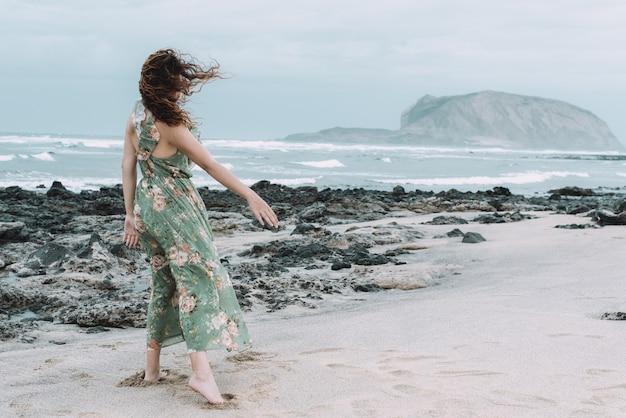 Młoda kobieta widziana od tyłu w zwiewnej kwiecistej sukience w wietrzny dzień na wyspie la graciosa
