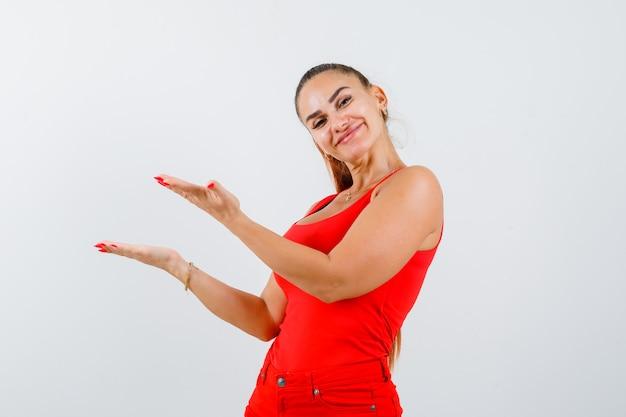 Młoda kobieta wita coś w czerwonym podkoszulku, spodniach i ładnie wyglądający widok z przodu.