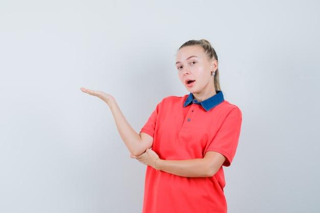 Młoda kobieta wita lub pokazuje coś w koszulce i wygląda pewnie. przedni widok.