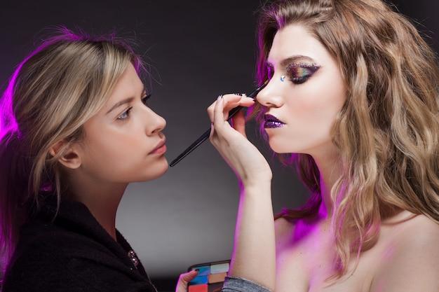Młoda kobieta wizażystka robi jasny makijaż mody. piękna dziewczyna z kreatywnych makijaż. atrakcyjna blondynka, zbliżenie