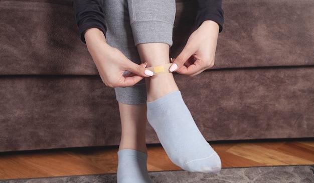 Młoda kobieta wkłada bandaż samoprzylepny w nogę.