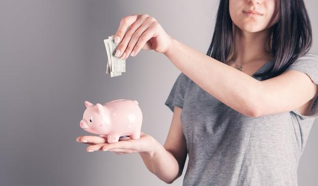 Młoda kobieta wkłada banknot do skarbonki