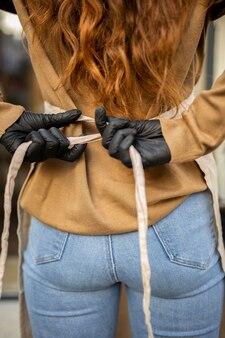 Młoda kobieta wkłada fartuch