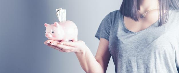 Młoda kobieta wkłada monetę do skarbonki jako oszczędności na inwestycję
