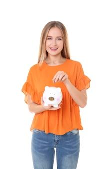 Młoda kobieta wkłada monetę do skarbonki