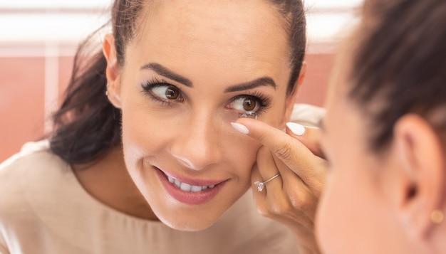 Młoda kobieta wkłada sobie soczewki kontaktowe do oczu rano w łazience przed lustrem.
