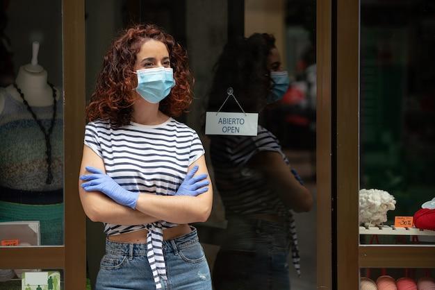 Młoda kobieta właściciel małej firmy w masce