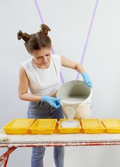 Młoda kobieta wlewa farbę do plastikowej tacki z farbą