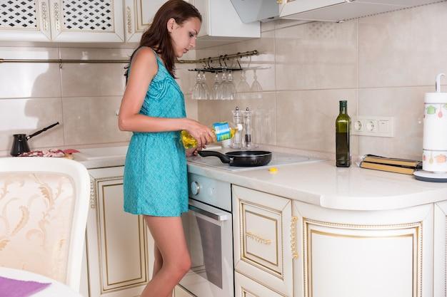 Młoda kobieta wlewając olej na patelni umieszczonej na górze palnika w kuchni.