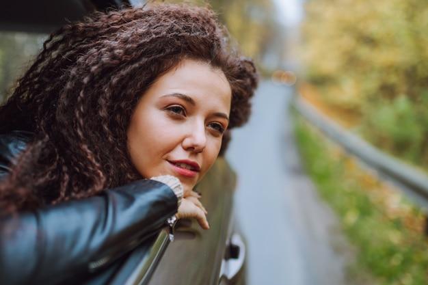 Młoda kobieta włosy afro podróż samochodem na drodze jesień dzikiego lasu. kobiece spojrzenie w otwartym oknie z tyłu siedzieć z radosnym uśmiechem.