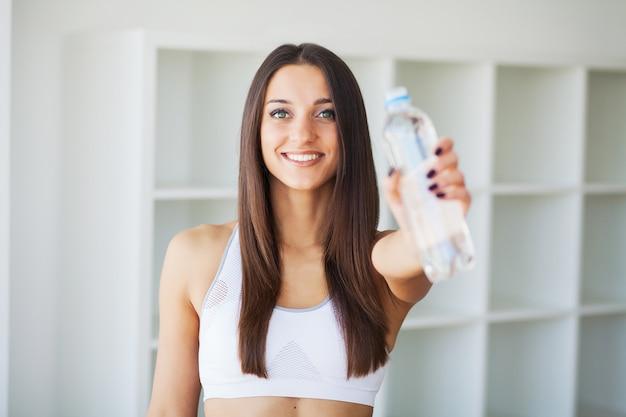 Młoda kobieta wody pitnej. piękna młodej dziewczyny mienia butelka woda