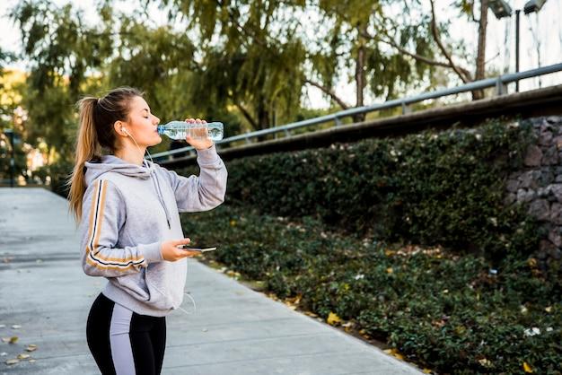 Młoda kobieta wody pitnej z butelki