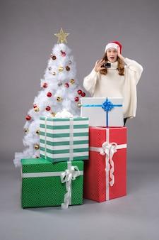 Młoda kobieta wokół prezentów świątecznych na szarej podłodze święto nowego roku boże narodzenie