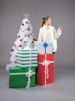 Młoda kobieta wokół świątecznych prezentów na szaro