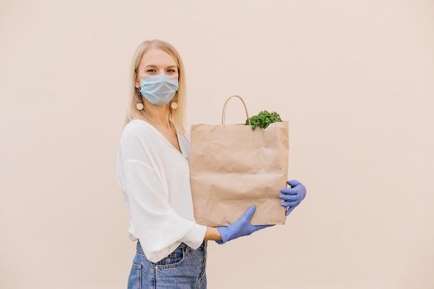 Młoda kobieta wolontariuszka kurier w masce ochronnej trzyma papierową torbę z produktami
