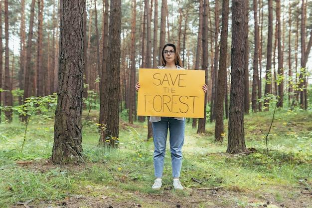 Młoda kobieta wolontariuszka w lesie pikietuje i trzyma plakat ratowania lasu