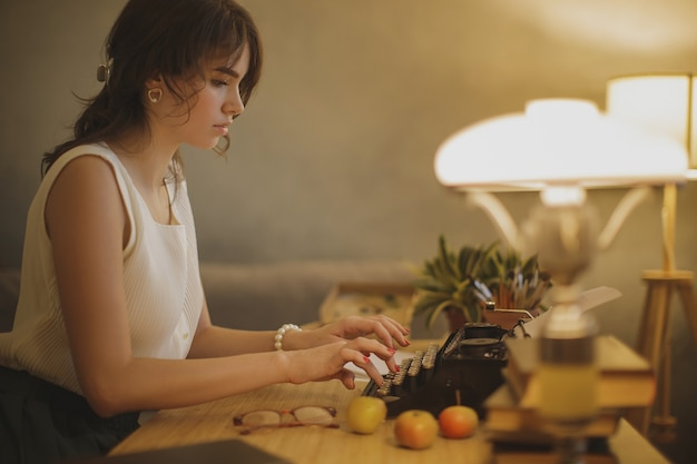 Młoda kobieta, wpisując na maszynie do pisania.
