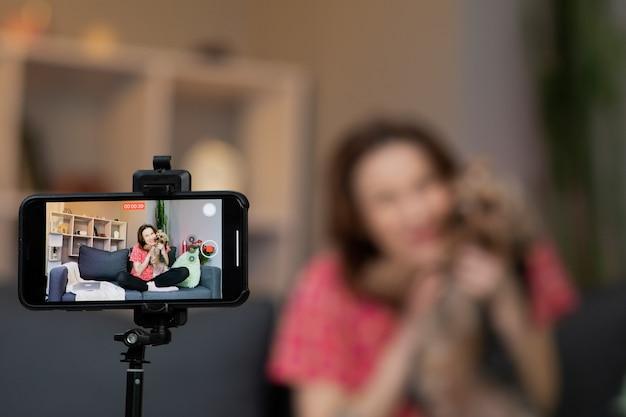 Młoda kobieta wpływowa vlogger siedzi w domu, mówiąc, patrząc na kamery i rejestrując wideokonferencje.