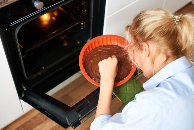 Młoda kobieta wprowadzenie deser w piekarniku