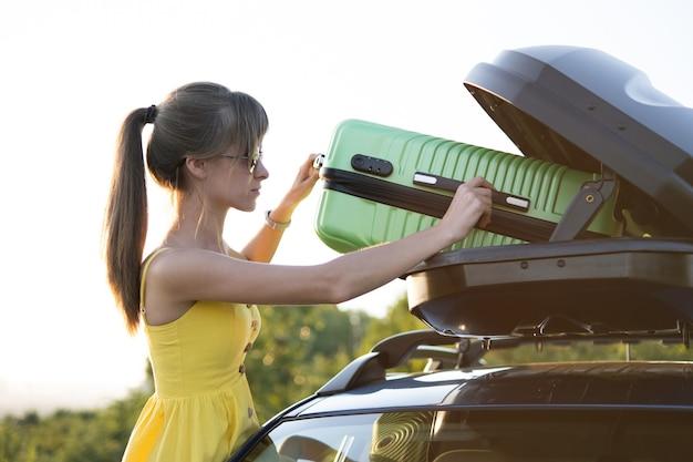 Młoda kobieta wprowadzenie zielonej walizki wewnątrz bagażnik samochodowy. koncepcja podróży i wakacji.
