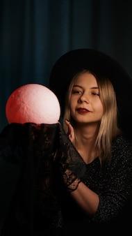 Młoda kobieta wróżka w kapeluszu trzyma magiczną piłkę. piękna psychiczna kobieta zgaduje czerwoną magiczną kulą