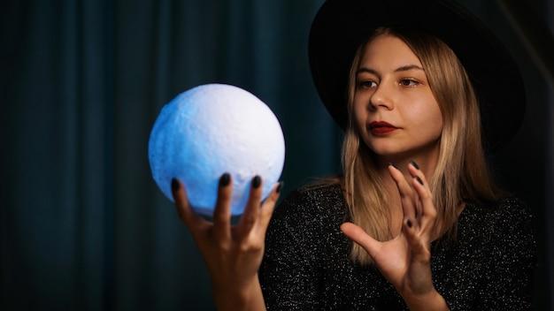 Młoda kobieta wróżka w kapeluszu trzyma magiczną piłkę. piękna psychiczna kobieta zgaduje niebieską magiczną kulą