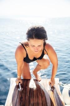 Młoda kobieta wsiada na jachcie na morzu przy słonecznym dniem