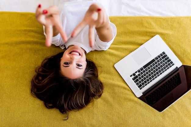 Młoda kobieta wskazał znak zwycięstwa, leżąc w łóżku z laptopem z góry. widok z góry.