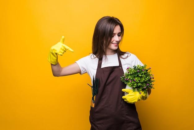 Młoda kobieta wskazała na roślinę na białym tle