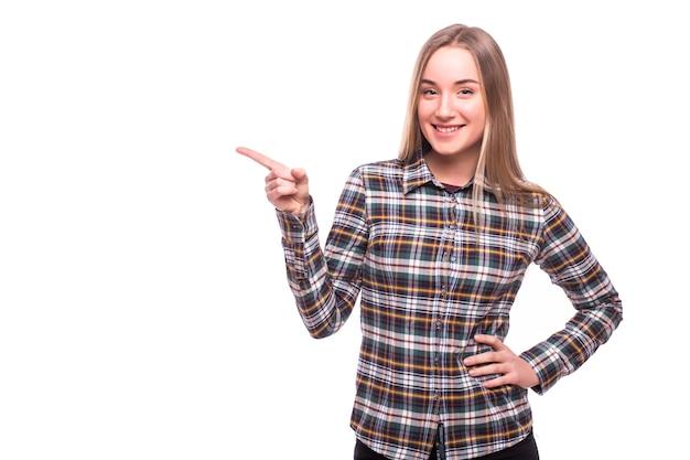 Młoda kobieta wskazała stronę z uśmiechem na białym tle na białej ścianie