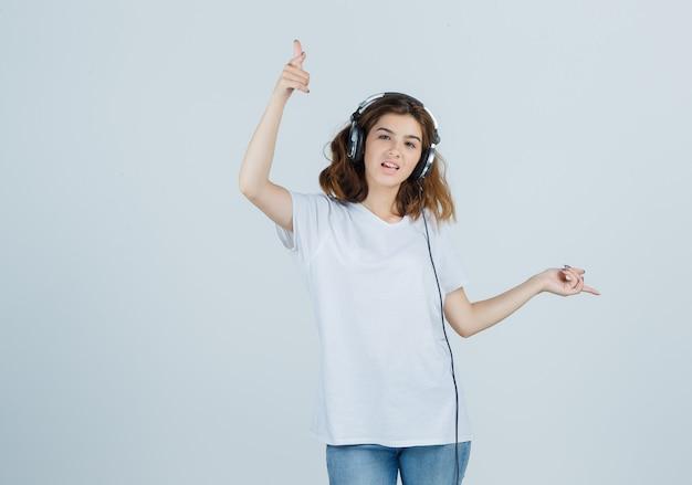 Młoda kobieta wskazując dalej podczas słuchania muzyki w słuchawkach w białej koszulce, dżinsach i patrząc szczęśliwy, widok z przodu.
