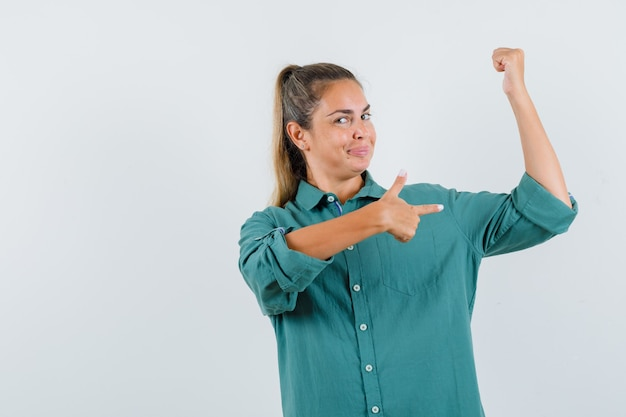 Młoda kobieta wskazując mięśnie palcem wskazującym w zielonej bluzce i wygląda atrakcyjnie