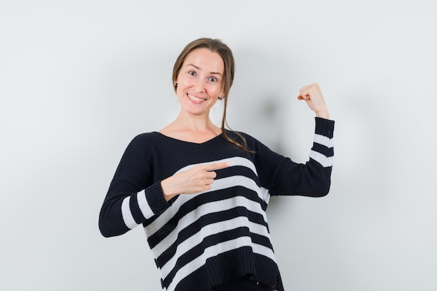 Młoda kobieta wskazując mięśnie w czarną bluzkę i czarne spodnie i patrząc szczęśliwy