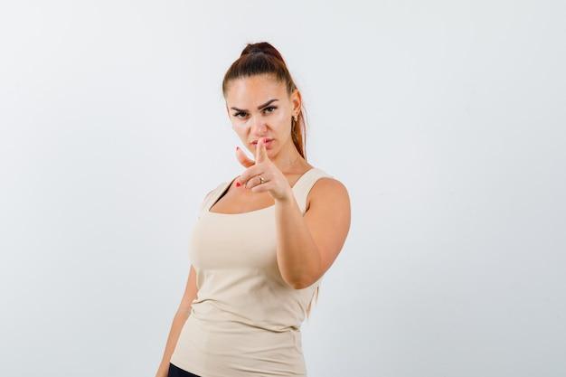 Młoda kobieta, wskazując na aparat w beżowym podkoszulku bez rękawów i patrząc pewnie. przedni widok.