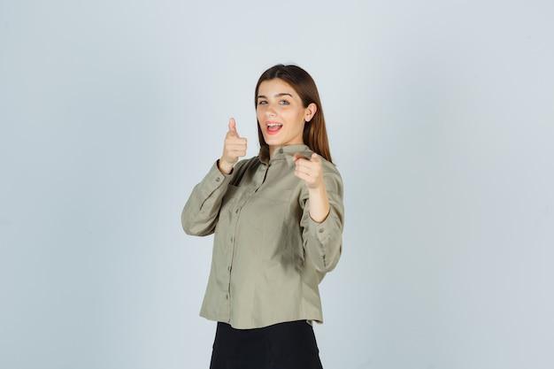Młoda kobieta, wskazując na aparat w koszuli, spódnicy i patrząc szczęśliwy