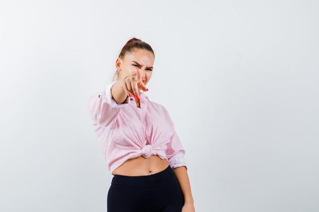 Młoda kobieta, wskazując na aparat w zwykłej koszuli i patrząc pewnie. przedni widok.