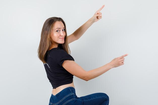 Młoda kobieta, wskazując na bok, klęcząc w czarnej bluzce i wyglądając na zadowolonego