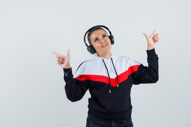 Młoda kobieta wskazując na bok podczas słuchania muzyki w kolorowej bluzie, słuchawkach i patrząc rozbawiony. przedni widok.